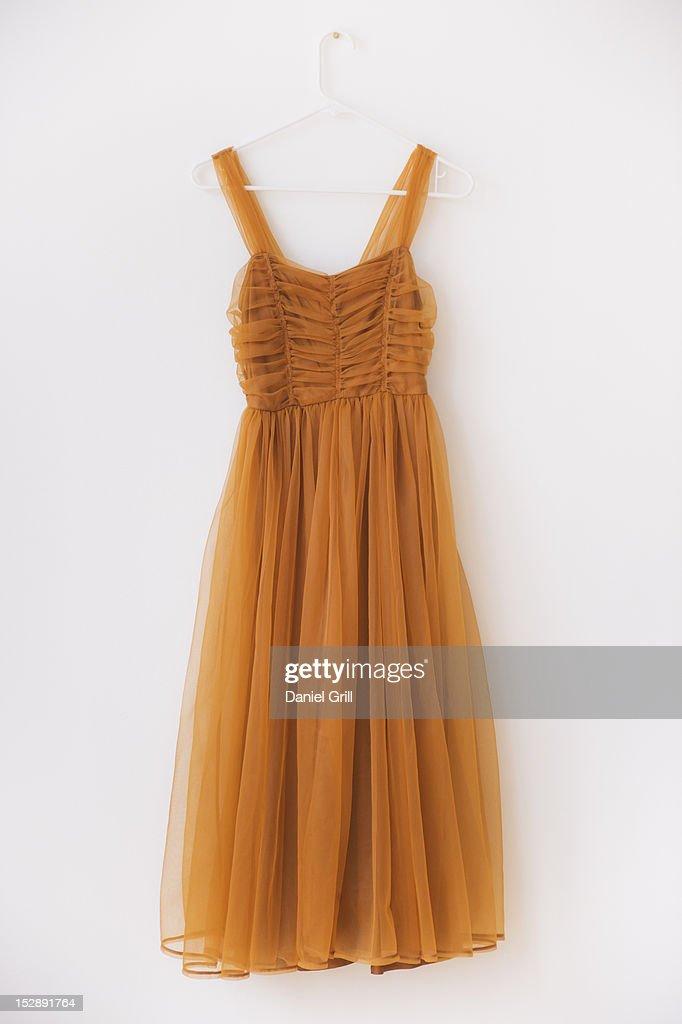 Shiffon dress on hanger against white wall