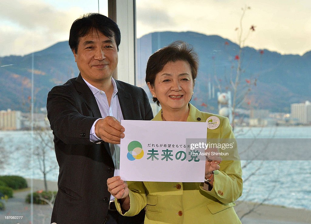 Shiga Prefecture governor <a gi-track='captionPersonalityLinkClicked' href=/galleries/search?phrase=Yukiko+Kada&family=editorial&specificpeople=7765393 ng-click='$event.stopPropagation()'>Yukiko Kada</a> (R) and the party's acting president Tetsunari Iida display their new anti-nuclear party 'Nippon Mirai no To (Japan Future Party)' logo during a press conference on November 27, 2012 in Otsu, Shiga, Japan. With Ichiro Ozawa's People's Life Party and other small parties joining, 'the third force' will be split into either Japan Future Party or Japan Restoration Party.