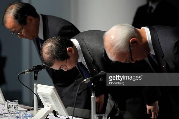 Shigehisa Takada chairman and president of Takata Corp center bows with Hiroshi Shimizu executive vice president of Takata Corp left and Yoichiro...