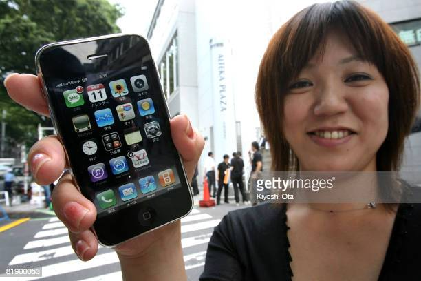 Shiho Hishida poses with her new Apple iPhone outside SoftBank Mobile's flagship store on the first day of its Japanese launch on July 11 2008 in...