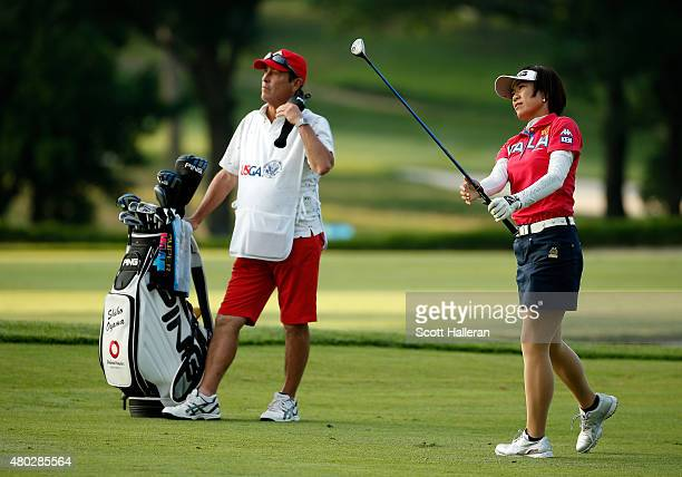 Shiho Oyama of Japan watches her second shot on the ninth hole as her caddie Dana Derouaux looks on during the second round of the US Women's Open at...