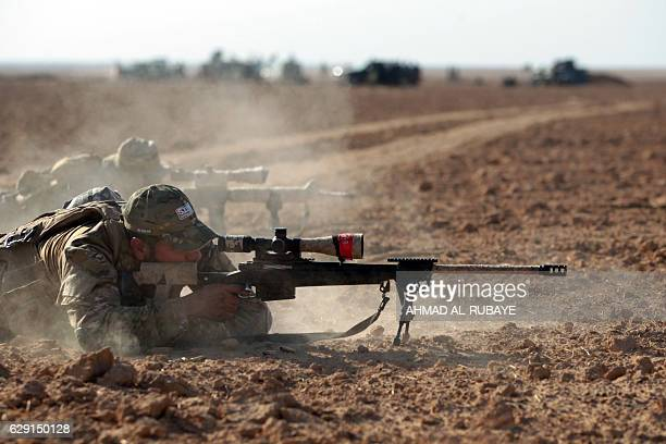 TOPSHOT Shiite fighters from the Hashed alShaabi paramilitary forces fire towards enemy position as they advance towards the Iraqi town Shwah west of...