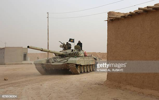 Shiite fighters from the Hashed alShaabi paramilitary units drive a tank as they enter the village of Shwah south of the city of Tal Afar on the...