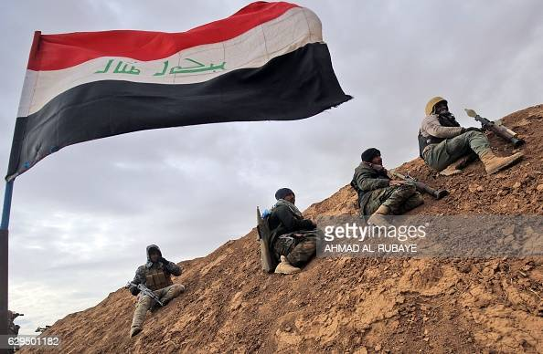 TOPSHOT Shiite fighters from the Hashed alShaabi paramilitary units sits under an Iraqi flag as they advance towards the village of Shwah south of...