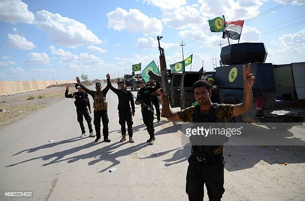 Shiite fighters from the Popular Mobilisation units celebrate next to their vehicles inside the northern Iraqi city of Tikrit on March 31 2015 during...