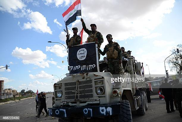 Shiite fighters from the Popular Mobilisation units celebrate on a truck with a national flag and a board they seized from the Islamic State group on...