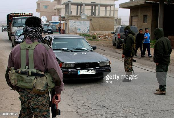 Shiite gunmen block vehicles on a road in the village of Bazzaliyeh which leads the eastern Lebanese town of Arsal in the Bekaa valley near the...