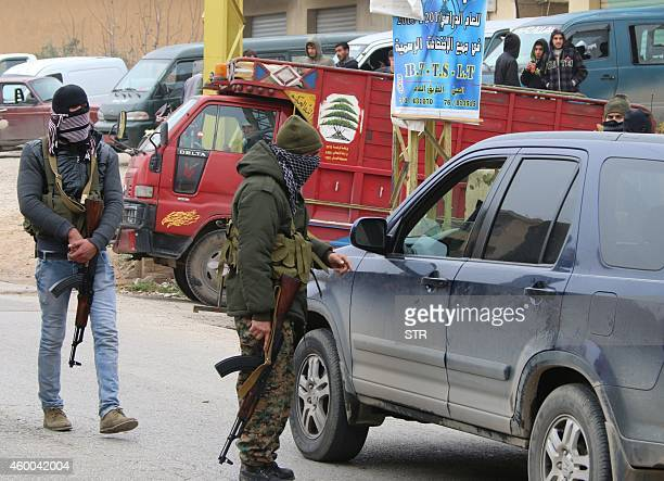 Shiite gunmen check vehicles on a road in the village of Bazzaliyeh which leads the eastern Lebanese town of Arsal in the Bekaa valley near the...