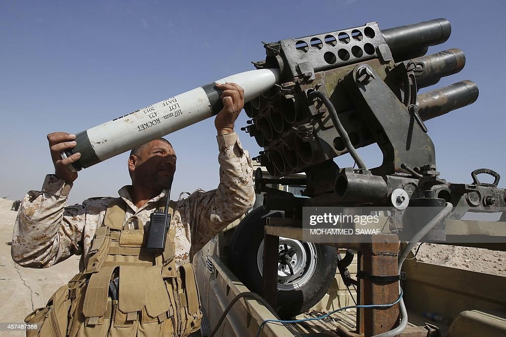 A Shiite Iraqi fighter loyal to Grand Ayatollah Ali alSistani loads a missile launcher during clashes with Islamic State militant group fighters in...