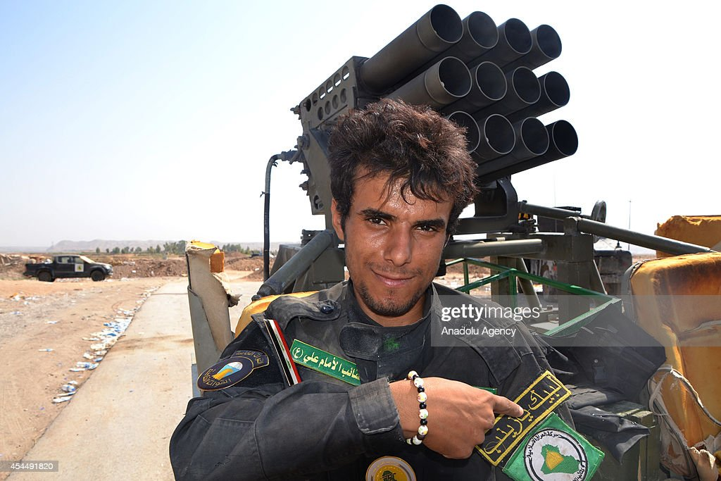 Shiite militia shows his coat of arms in front of a heavy weapon following clashes of Iraqi forces for seizing the village of Sulaiman Bek located...