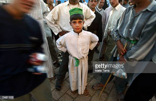 Shiite Muslim boy wears traditional clothing while gathered outside the shrine of Imam Ali the soninlaw of Mohammed to mark the anniversary of the...