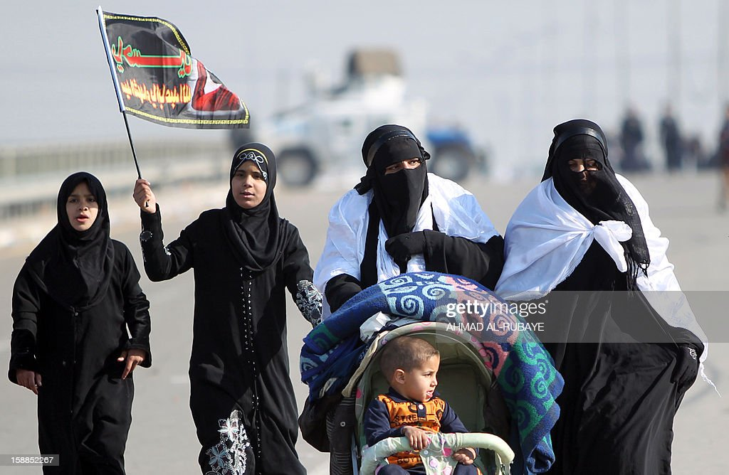 Shiite Muslim female pilgrims march along the main highway that links the Iraqi capital Baghdad with the central shrine city of Karbala on January 1, 2013, to take part in the Arbaeen religious festival which marks the 40th day after Ashura commemorating the seventh century killing of Prophet Mohammed's grandson, Imam Hussein.