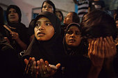 Shi'ite Muslim girls pray during the second night of Ashura a commemoration involving running over fiery coals to mourn the martyrdom of Husayn ibn...