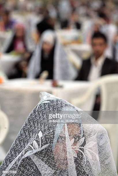 A Shiite Muslim Iraqi bride looks over from under her veil during a mass wedding in the stadium at Baghdad University part of the celebrations for...