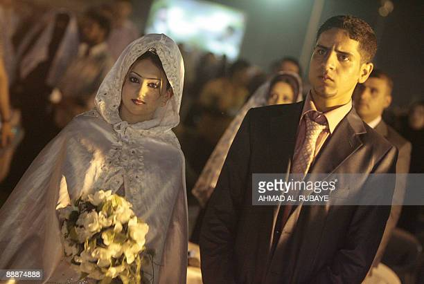 A Shiite Muslim Iraqi couple attend a mass wedding in the stadium at Baghdad University part of the celebrations for the birth of Imam Ali the...
