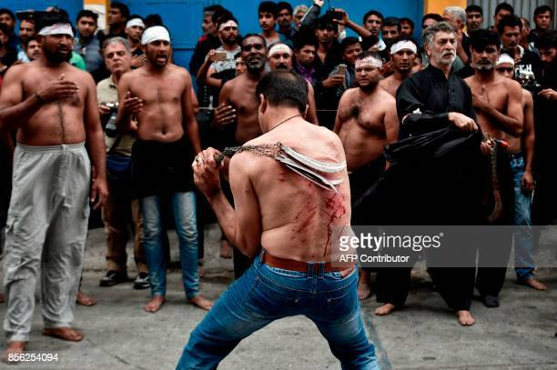 Shiite Muslim migrants lash themselves during the celebrations of the Shiite religious holiday of Ashura at an industrial area of Piraeus near Athens...