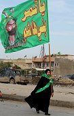 A Shiite Muslim pilgrim carries a flag as she walks on a road in the southern outskirts of the Iraqi capital Baghdad on November 30 as tens of...