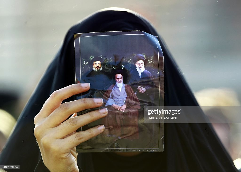 A Shiite Muslim pilgrim holds up a picture of Iranian supreme leader Ayatollah Ali Khamenei (R), Iran's late founder of the Islamic Republic Ayatollah Ruhollah Khomeini (C), and the head of Lebanon's militant Shiite Muslim movement Hezbollah, Hassan Nasrallah, during a break in Najaf on their way to the shrine central city of Karbala on December 9, 2014 where they take part in the Arbaeen religious festival which marks the 40th day after Ashura which commemorates the seventh century killing of Prophet Mohammed's grandson, Imam Hussein. In addition to the millions of Shiite devotees who flock to Karbala, some of them on foot, from across Iraq, a large contingent of Iranians traditionally make the trip.