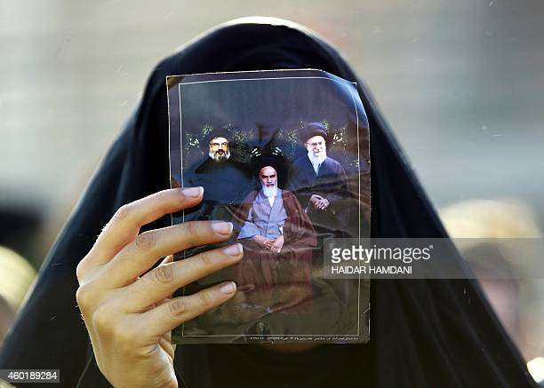 A Shiite Muslim pilgrim holds up a picture of Iranian supreme leader Ayatollah Ali Khamenei Iran's late founder of the Islamic Republic Ayatollah...