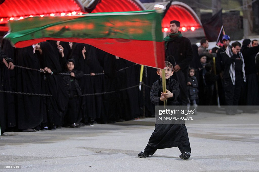 A Shiite Muslim pilgrim waves a huge flag at the Imam Hussein shrine during a ceremony marking Ashura in the holy city of Karbala some 80 kilometers (50 miles) southwest of Baghdad, on November 24, 2012, as Shiites around the world remember the slaying of the Prophet Mohammed's grandson the Imam Hussein in the seventh century. Millions of people flood Karbala for the peak of the Ashura rituals, which occurs on November 25 this year. AFP PHOTO / AHMAD AL-RUBAYE