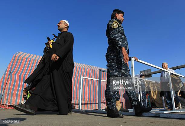 Shiite Muslim pilgrims undergo security checks on a main road in Baghdad's Dora district on November 30 as tens of thousands of observant Shiites...