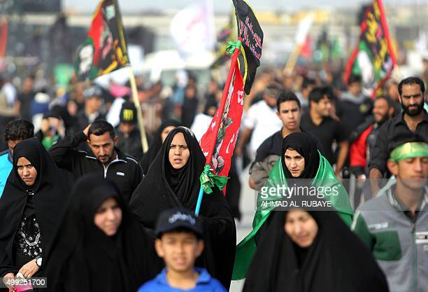 Shiite Muslim pilgrims walk on a road in the southern outskirts of the Iraqi capital Baghdad on November 30 as tens of thousands of observant Shiites...
