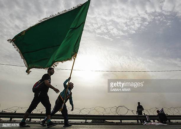 TOPSHOT Shiite Muslim pilgrims walk on a road on the southern outskirts of Baghdad as they head towards the holy city of Karbala on November 17 2016...