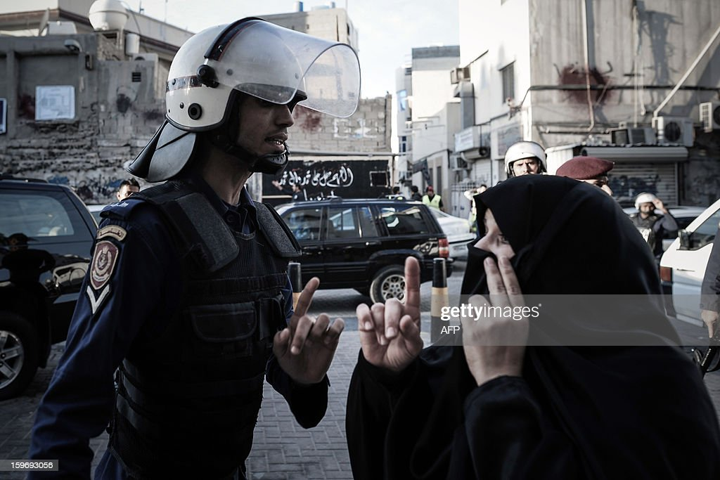 A Shiite Muslim woman argues with a riot policeman on the side of a demonstration called for by the February 14 Youth Coalition, an Internet group that regularly calls for protests in the Shiite-majority kingdom on January 18, 2013 in the capital Manama. Bahrain's government said the demonstration had not been authorised and warned security forces would prevent it from going ahead. AFP PHOTO/MOHAMMED ALSHAIKH