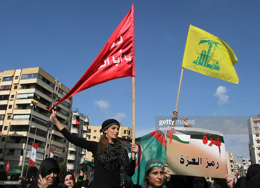 A Shiite Muslim woman holds up a flag as she listens to a screened speech by Hassan Nasrallah, the head of Lebanon's militant Shiite Muslim movement Hezbollah, as thousands gathered in the southern suburbs of the Lebanese capital Beirut on November 25, 2012, to mark Ashura, commemorating the death of Imam Hussein, grandson of the Prophet Mohammed, who was killed in 680 AD by the armies of the caliph Yazid in present day Iraq.