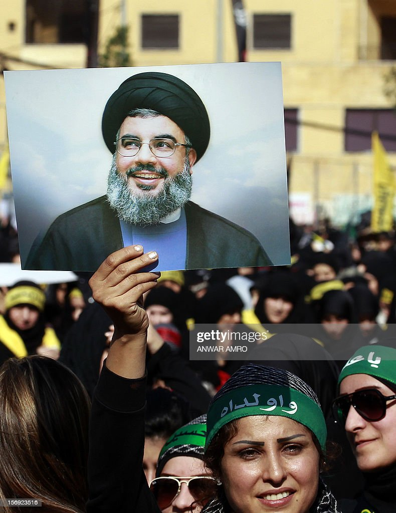 A Shiite Muslim woman holds up a photo of Hassan Nasrallah, the head of Lebanon's militant Shiite Muslim movement Hezbollah, as thousands gathered to listen to his screened speech in the southern suburbs of the Lebanese capital Beirut on November 25, 2012, to mark Ashura, commemorating the death of Imam Hussein, grandson of the Prophet Mohammed, who was killed in 680 AD by the armies of the caliph Yazid in present day Iraq.