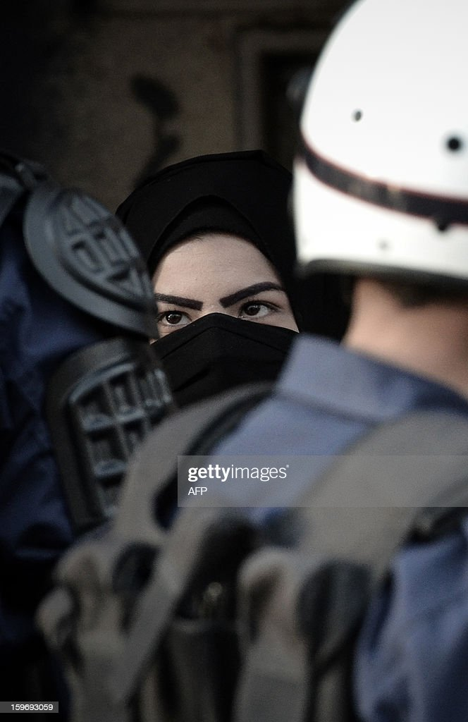 A Shiite Muslim woman looks at a riot policeman during a demonstration called for by the February 14 Youth Coalition, an Internet group that regularly calls for protests in the Shiite-majority kingdom on January 18, 2013 in the capital Manama. Bahrain's government said the demonstration had not been authorised and warned security forces would prevent it from going ahead. AFP PHOTO/MOHAMMED ALSHAIKH