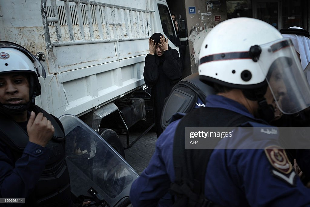 A Shiite Muslim woman rubs her eyes near riot policemen after being pepper sprayed while helping a woman being arrested during a demonstration called for by the February 14 Youth Coalition, an Internet group that regularly calls for protests in the Shiite-majority kingdom on January 18, 2013 in the capital Manama. Bahrain's government said the demonstration had not been authorised and warned security forces would prevent it from going ahead. AFP PHOTO/MOHAMMED ALSHAIKH