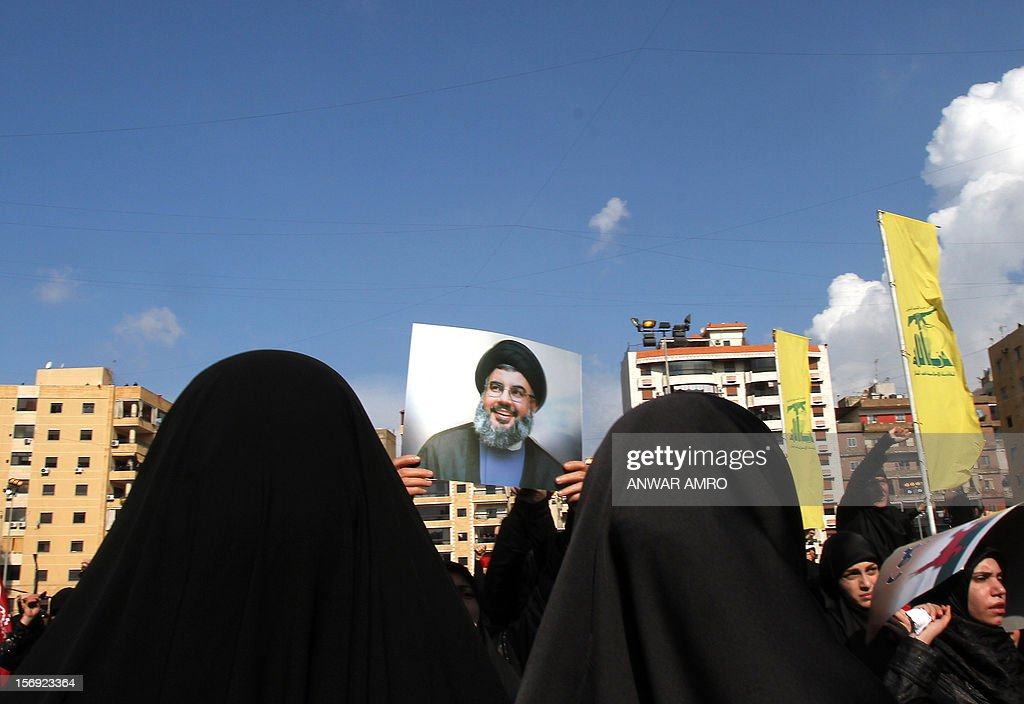 Shiite Muslim women hold up a photo of Hassan Nasrallah, the head of Lebanon's militant Shiite Muslim movement Hezbollah, as thousands gathered to listen to his screened speech in the southern suburbs of the Lebanese capital Beirut on November 25, 2012, to mark Ashura, commemorating the death of Imam Hussein, grandson of the Prophet Mohammed, who was killed in 680 AD by the armies of the caliph Yazid in present day Iraq.