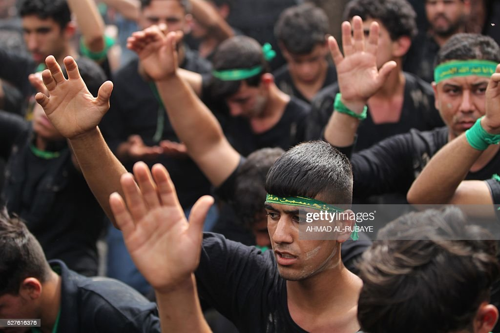 Shiite Muslim worshippers beat their chests and heads as they gather outside the Imam al-Kadhim shrine during a ceremony to mark the anniversary of the death of the religious figure on May 3, 2016, in the northern district of Kadhimiya in the Iraqi capital Baghdad. The commemoration of the 799 AD death of Shiite Islams revered seventh Imam, who is believed to have been poisoned by agents of then Sunni ruler Harun al-Rashid, culminates today. / AFP / AHMAD