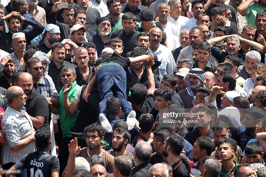 Shiite Muslim worshippers carry a man who fainted during a ceremony at the Imam al-Kadhim shrine to mark the anniversary of the death of the religious figure on May 3, 2016, in the northern district of Kadhimiya in the Iraqi capital Baghdad. The commemoration of the 799 AD death of Shiite Islams revered seventh Imam, who is believed to have been poisoned by agents of then Sunni ruler Harun al-Rashid, culminates today. / AFP / AHMAD
