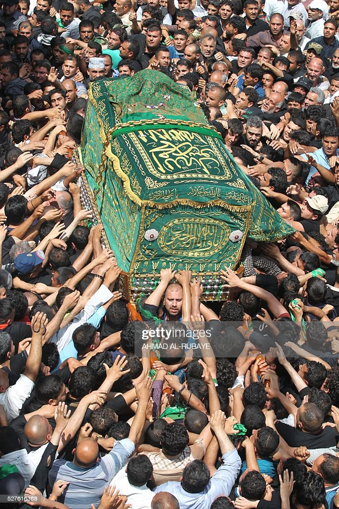 Shiite Muslim worshippers carry a mock coffin at the Imam al-Kadhim shrine as they gather to mark the anniversary of the death of the eighth century revered Imam on May 3, 2016, in the northern district of Kadhimiya in the Iraqi capital Baghdad. The commemoration of the 799 AD death of Shiite Islams revered seventh Imam, who is believed to have been poisoned by agents of then Sunni ruler Harun al-Rashid, culminates today. / AFP / AHMAD