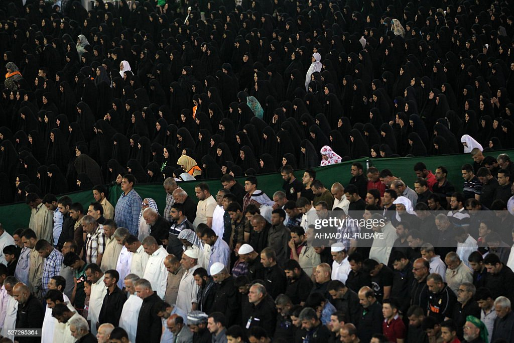 Shiite Muslim worshippers pray as they gather outside the Imam al-Kadhim shrine late on May 2, 2016, in the northern district of Kadhimiya in the Iraqi capital Baghdad. The commemoration of the 799 AD death of Shiite Islams revered seventh Imam, who is believed to have been poisoned by agents of then Sunni ruler Harun al-Rashid, is due to culminate on May 3. / AFP / AHMAD