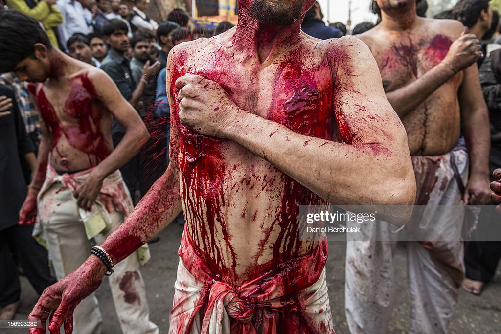 Shiite Muslims beat their chests, holding razor blades, as part of a self-flagellation ritual during a religious procession marking Ashura on November 25, 2012 in New Delhi, India. The religious festival of Ashura, which involves a ten-day mourning period starting with the first day of Muharram on the Islamic calendar, commemorates and mourns the seventh-century martyrdom of Prophet Muhammad's grandson Imam Hussein in the battle of Karbala.