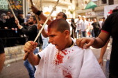 Shiite Muslims bleed as they gash their foreheads with swords and beat themselves during a ceremony marking Ashura in Nabatiyeh southern Lebanon on...