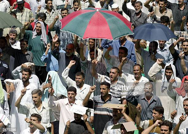 Shiite Muslims chant beneath the hot midday sun during the Friday noon prayers at the Shiite Kazimiya Mosque 05 September 2003 in Baghdad one week...