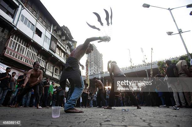 Shi'ite Muslims flagellate themselves during a Muharram procession ahead of Ashoura in Mumbai India on November 4 2014 Ashoura which falls on the...