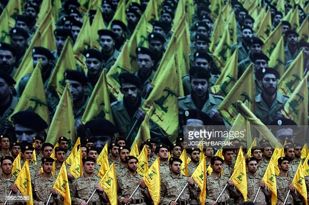 Shiite Muslims Hezbollah militants stand to attention as hundreds of people gather in a huge hall waiting to watch a televised speech by Hassan...