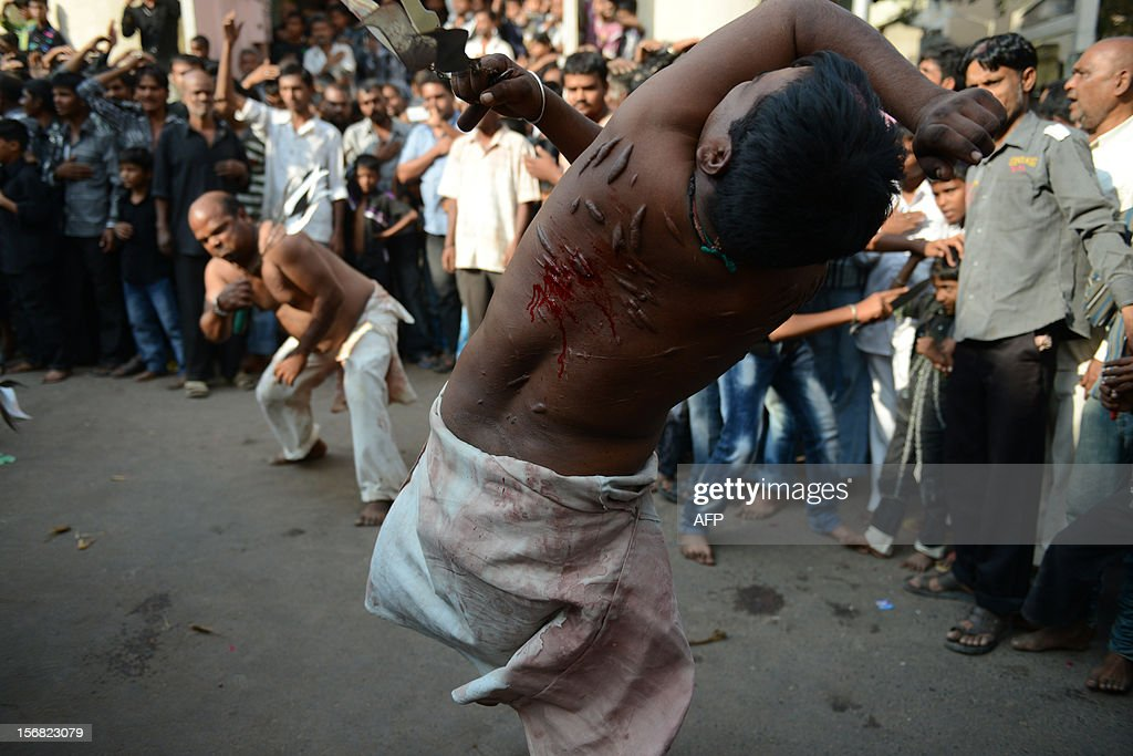 Shiite Muslims perform ritual acts of self flagelation with a cluster of knives and chains during a religious procession in Ahmedabad on November 22, 2012. Rituals are held on the seventh day of Moharram, which commemorates the seventh century slaying of the Prophet Mohammed's grandson in southern Iraq. During the holy month of Muharram, large processions are formed and the devotees parade the streets holding banners and carrying models of the mausoleum of Hazrat Imam Hussain and his people, who fell at Karbala. Muslims show their grief and sorrow by inflicting wounds on their own bodies with sharp metal tied to chain with which they scourge themselves, in order to depict the sufferings of the martyrs AFP PHOTO / Sam PANTHAKY