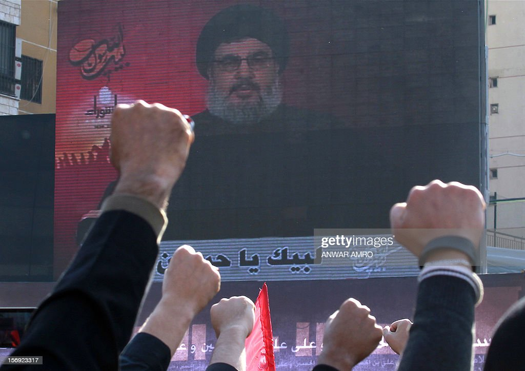 Shiite Muslims punch the air as they listen to a screened speech by Hassan Nasrallah, the head of Lebanon's militant Shiite Muslim movement Hezbollah, as thousands gathered in the southern suburbs of the Lebanese capital Beirut on November 25, 2012, to mark Ashura, commemorating the death of Imam Hussein, grandson of the Prophet Mohammed, who was killed in 680 AD by the armies of the caliph Yazid in present day Iraq.