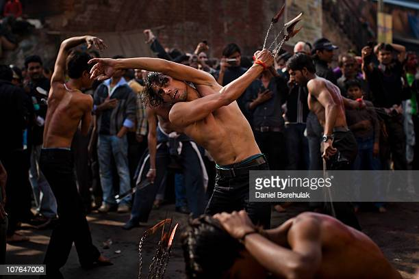 Shiite Muslims take part in a selfflagelation ritual during a religious procession of the Ashura mourning period on December 17 2010 in New Delhi...