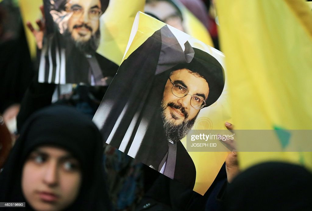A Shiite supporter holds a poster showing Hassan Nasrallah, the head of Lebanon's militant Shiite Muslim movement Hezbollah, as he addresses supporters through a giant screen during a meeting in Beirut's southern suburb of Mujammaa Sayyed al-Shuhada on January 30, 2014. Hezbollah chief said he does not want war with Israel, after the Israeli military shelled border areas following a Hezbollah attack that left two Israeli soldiers dead.