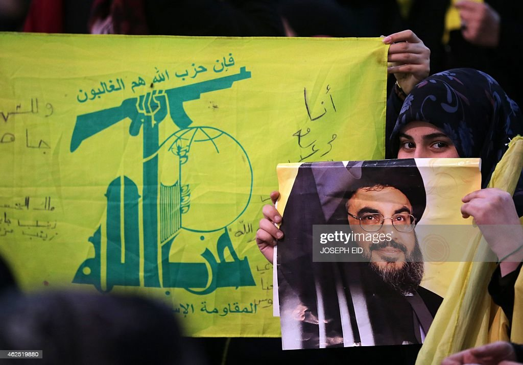 A Shiite supporter holds a poster showing <a gi-track='captionPersonalityLinkClicked' href=/galleries/search?phrase=Hassan+Nasrallah&family=editorial&specificpeople=615774 ng-click='$event.stopPropagation()'>Hassan Nasrallah</a>, the head of Lebanon's militant Shiite Muslim movement Hezbollah, as he addresses supporters through a giant screen during a meeting in Beirut's southern suburb of Mujammaa Sayyed al-Shuhada on January 30, 2014. Hezbollah chief said he does not want war with Israel, after the Israeli military shelled border areas following a Hezbollah attack that left two Israeli soldiers dead. AFP PHOTO/JOSEPH EID