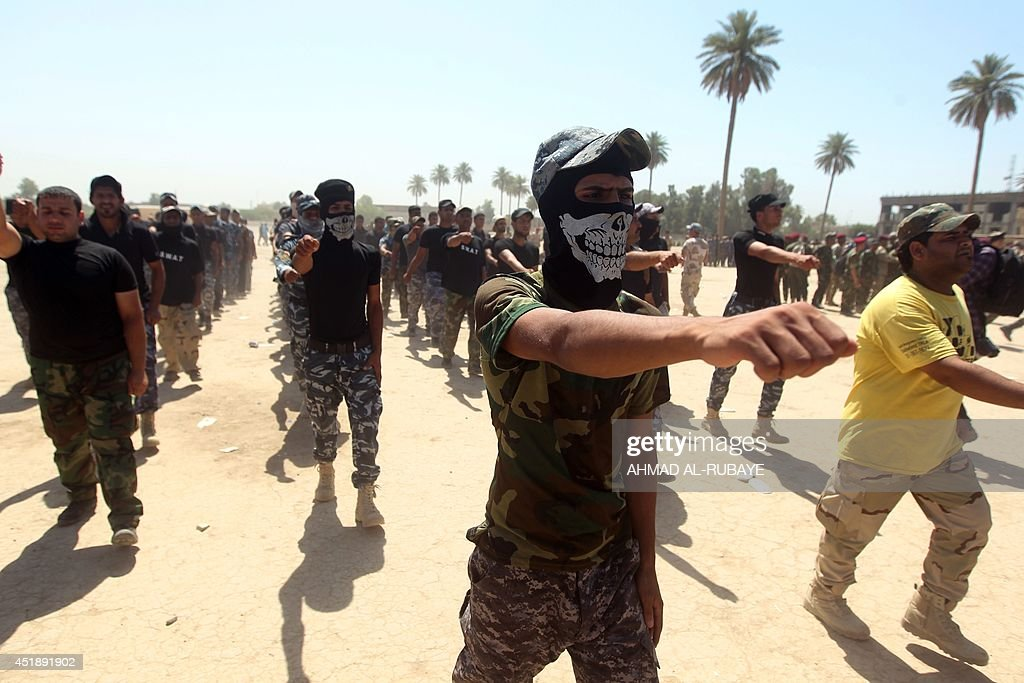 Shiite volunteers from the Iraqi Ketaeb Hezbollah march as they join the Iraqi army to fight against Jihadist militants of the Islamic State formerly...