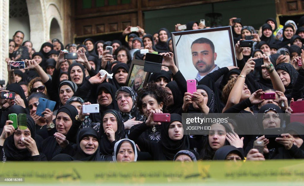 Shiite women mourn and take photos during the funeral of Hezbollah militants in Shiah, a southern suburb of the Lebanese capital, who were killed in the suicide attack outside the Iranian Embassy in Beirut the previous day, on November 20, 2013. Thousands of people turned out for a funeral for the four Iranian embassy security guards, all of whom were members of Lebanon's powerful Shiite movement Hezbollah, which is also backed by Iran and is fighting alongside Assad's troops against Sunni-led rebels.