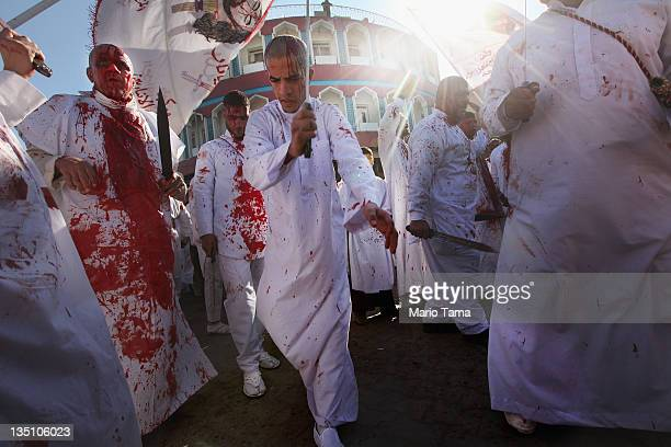 Shi'ite worshipers bleed while cutting their scalps in a ritual display of mourning during an Ashura commemoration ceremony outside Kadhimiya shrine...